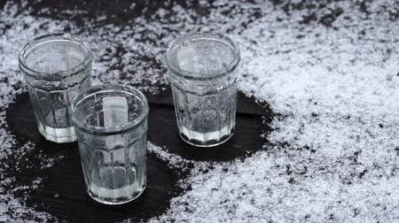 аперитив : Empty glasses of vodka standing on the wooden table covered with snow Стоковые видеозаписи