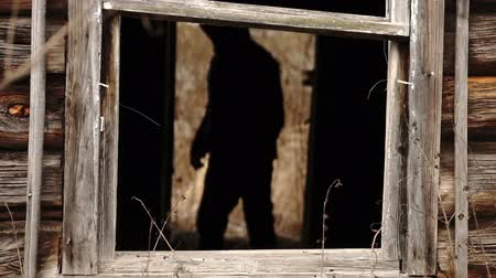 Male silhouette standing in a dark doorway of a destroyed abandoned wooden house Wideo