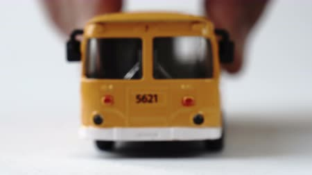 Male hand moving a toy bus towards the camera