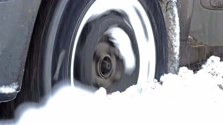 tread : Wheel of a car turns and slips in the deep snow