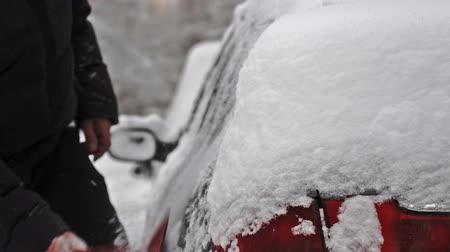 Man removing snow from a car after big snow storm