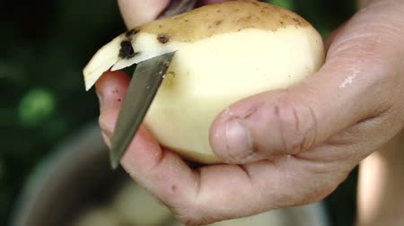 пюре : Female hands peeling potato close up. Slow motion.
