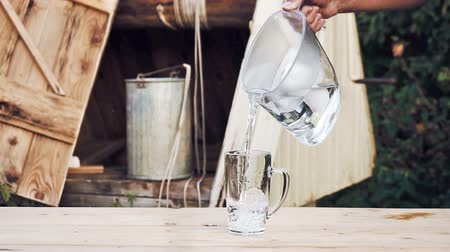 szűrés : Mans hand pours water from water filter jug into a glass cup on the wooden table with a village well on the background