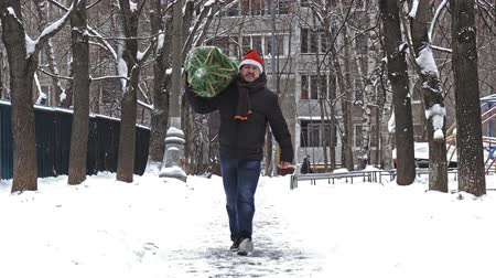 Man carries a Christmas tree packed in a grid just bought at the Christmas market Wideo