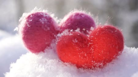 Two woolen hearts on the snow and backlighted by winter morning sun. Slow motion