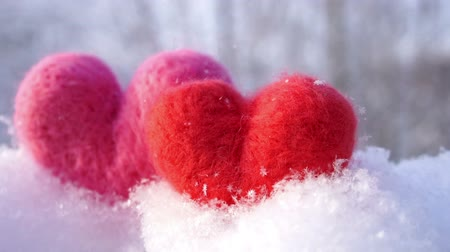 Two Valentines woolen hearts on the clear white snow in winter slow motion Wideo