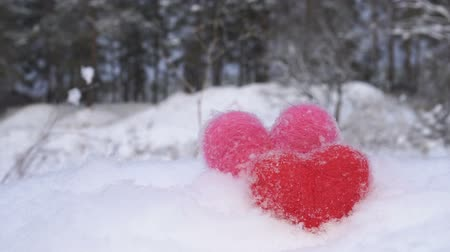 Red and pink woolen hearts on white snow in front of forest in winter