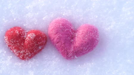 Red and pink woolen hearts on white snow in winter Wideo
