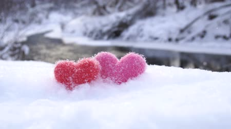 Red and pink woolen hearts on white snow on the river shore in winter