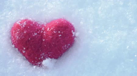 Red woolen heart on lying on the white clear snow in winter Wideo