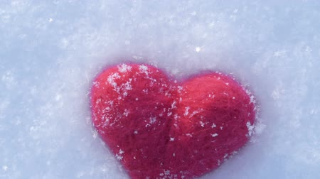Red woolen heart lying on white snow in winter camera movement in a circle Wideo