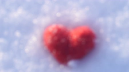 Camera approaches and focuses to the red woolen heart lying on the snow Wideo