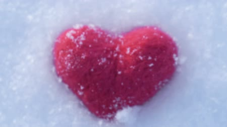 plüss : Ð¡amera moves away from and makes unfocused the red woolen heart lying on the snow