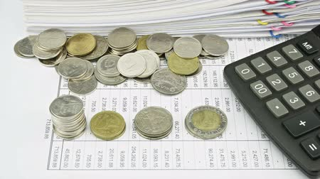 impostos : Counting and sort type of coins on finance account have pile overload paperwork report of sales and receipt with colorful paperclip and calculator as background time lapse. Business concept footage. Stock Footage