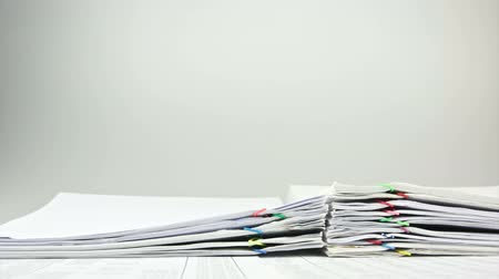 ataç : Overload paperwork of sales and receipts placed on table with white background time lapse. Pile of organized document is increasing up with colorful paperclip as work hard. Business concept footage. Stok Video