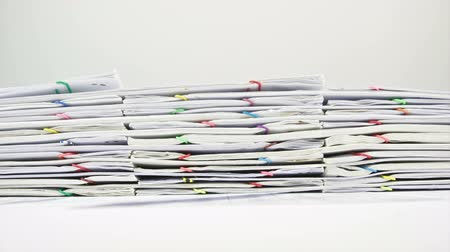 Stack paperwork of report of sales and receipts placed on table with white background  time lapse. Pile of overload messy document is increasing up with colorful paperclip. Business concept footage. Stok Video