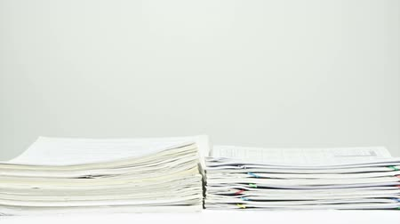 Stack old overload paperwork report of sales and receipt place on table with white background time lapse. Pile of organized document is increasing up with colorful paperclip. Business concept footage. Dostupné videozáznamy