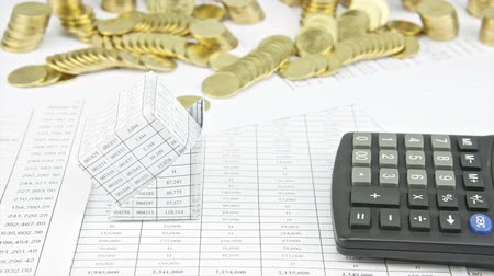 Bankruptcy of house and calculator with pile of gold coins on finance account as background time lapse. Pile of gold coins are falling as work is going bankrupt. Business concept footage. Dostupné videozáznamy