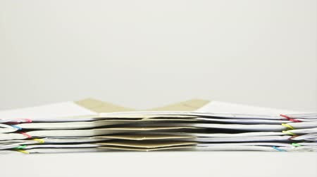 Envelope between stack paper report of sales and receipt with envelope place on table with white background time lapse. Pile of document is increasing as work hard. Business concept footage. Stok Video