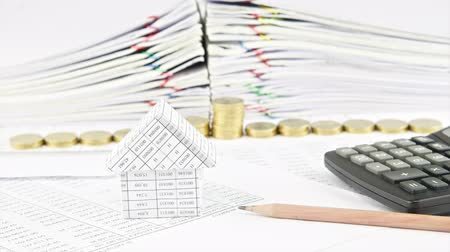 House and pencil with step pile of gold coins on finance account with stack old paper report of sales and receipt as background time lapse. Coins are increasing as success. Business concept footage.