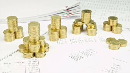 Pile of gold coins as tower on finance account have stack document report of sales time lapse. Pile of gold coins are increasing up as business growing and successful. Business concept footage.