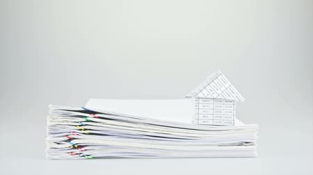 impostos : House on stack old paper report of sales and receipt with white background time lapse. Pile of document increasing with colorful paperclip as work is going to be successful. Business concept footage. Stock Footage