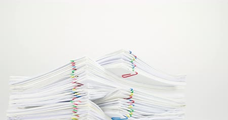 Pile of document overload with colorful paperclip place on table with white background time lapse. Pile of document is decreasing as work is going to be successful. Business concept footage. Stok Video