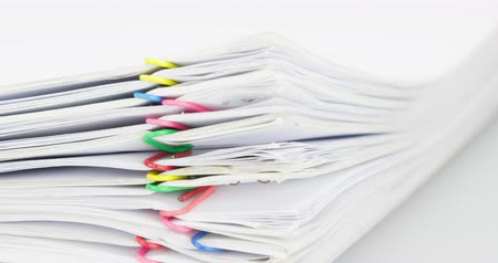 Close up colorful paper clip with pile of report have blur pile of paperwork as foreground and background time lapse. Document is increasing as work is going to be success. Business concept footage. Stok Video