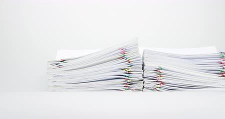 Pile of paper report and paperwork overload with colorful paperclip place on table time lapse. Pan follow pile of document is decreasing as work is going to be successful. Business concept footage. Stok Video