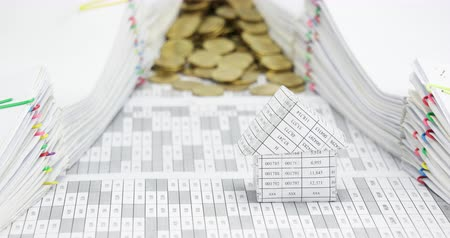 House with overflow of gold coins between pile of receipt overload with colorful paperclip place on table time lapse. Gold coin are increasing as work is going to be success. Business concept footage.