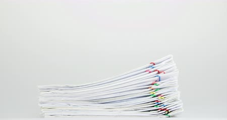 Stack paperwork of report and receipt overload with colorful paperclip place on white table time lapse.  Pile of document is increasing as work is going to be successful. Business concept footage.