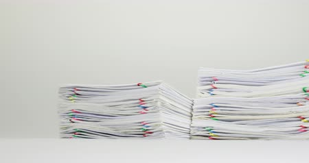 Stack overload paperwork of report and receipt with colorful paperclip place on white table time lapse. Pile of document is decreasing as work is going to be successful. Business concept footage.