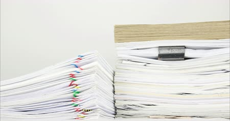 Overload stack document of report with colorful paperclip and brown envelope on paperwork place on white background time lapse. Pile document is decreasing as work success. Business concept footage. Stok Video