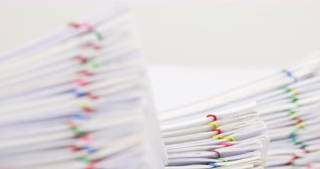 Pile overload paperwork of report with colorful paperclip have blur pile document as foreground and background with white background time lapse. Business concept successful footage.