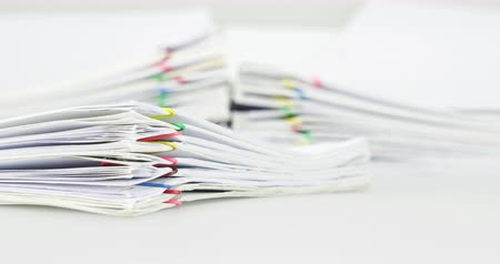 Pile overload document of report and receipt with colorful paperclip place on white background time lapse. Pile of document is increasing as work is going to be successful. Business concept footage.