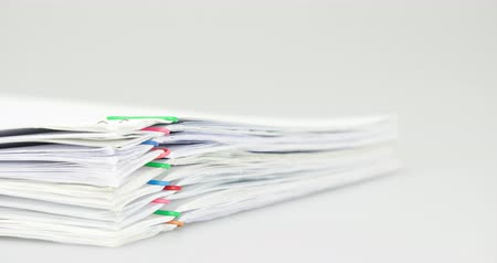 Pile overload paperwork of report with colorful paperclip place on white background time lapse.  Pile of document is decreasing with paperclip as work is going to be success. Business concept footage.