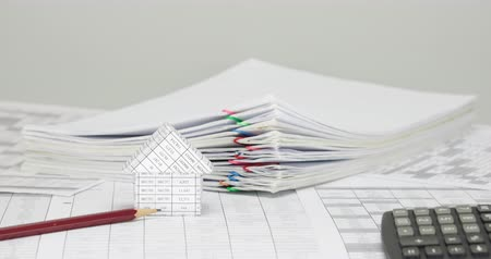 House and pencil on finance account have blur pile overload paper of report and receipt with colorful paperclip and calculator place on white background time lapse. Business concept success footage. Stok Video