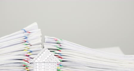 House have blur pile overload document of receipt and report with colorful paperclip place on white background time lapse. Pile of document is decreasing as work successful. Business concept footage.
