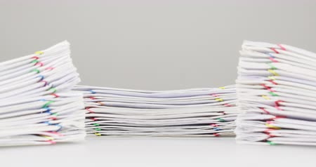 archívum : Pile overload paperwork of receipt and report with colorful paperclip have dual blur pile document foreground on white table time lapse. Document is increasing as successful. Business concept footage.