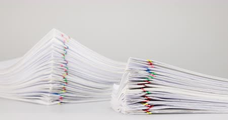 Pile overload paperwork of receipt and report with colorful paperclip from blur pile overload document are increasing place on white background time lapse. Business concept successful footage.
