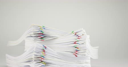 Pile overload document of report and report with colorful paperclip place on white background time lapse. Pile of document is decreasing with paperclip as work successful. Business concept footage.
