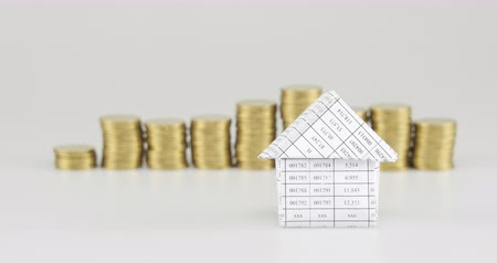House have blur pile of gold coins place on white background time lapse. Pile of gold coins are increasing wave as work is going to be successful. Business concept footage.