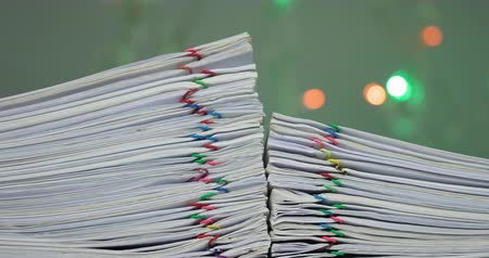 Stack of paperwork with colorful paperclip have colorful bokeh circle or defocused of glitter as background time lapse. Pile of document is increasing as work successful. Business concept footage.
