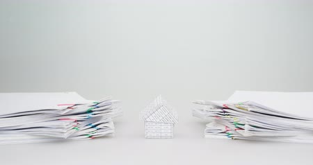 House between pile overload document of report and receipt with colorful paperclip have yellow and white engineer hat on top with white background time lapse. Business concept successful footage. Stok Video