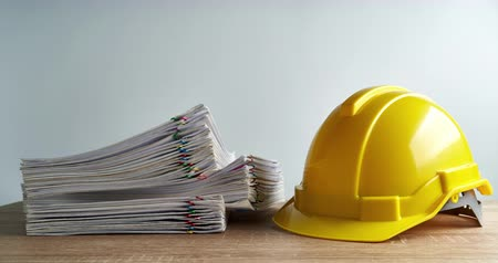 makbuz : Pile of overload paperwork report of sale and receipt with yellow engineer hat on wood table and white background with copy space time lapse. Business and finance concepts successful footage.