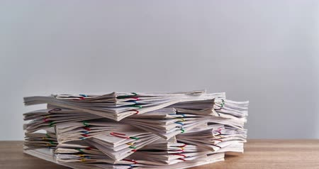 dosya : Pile overload document of report of sale and receipt with colorful paperclip place on wood table and white background with copy space time lapse. Business and finance concepts successful footage.