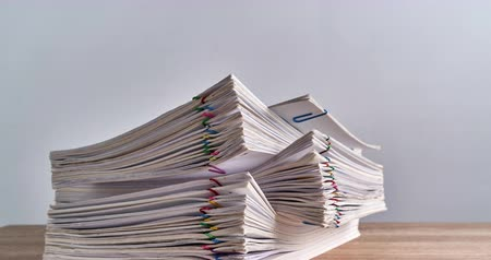 makbuz : Pile overload paperwork of report of sale and receipt with colorful paper clip place on wood table and white background with copy space time lapse. Business and finance concepts successful footage.