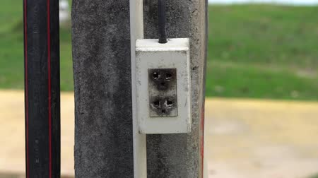 unplug : Closeup the electrical plug socket hanging and swinging on concrete electricity post background Stock Footage