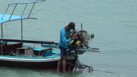 a man repairing motor Long Tailed Boat, off the Coast of Phuket Thailand Stockvideo