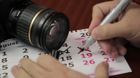 questionário : The photographers hand marks the date on the calendar with a marker. On the calendar is the camera